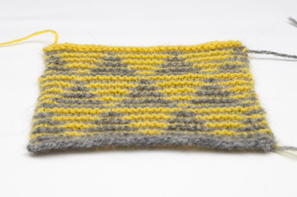 Strickprobe mit Dreiecken in grau und gelb in flacher Ansicht