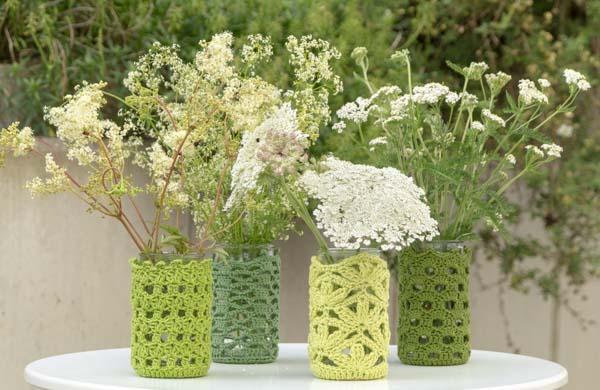 Vier Gläser mit grünem Garn behäkelt und Wiesenblumen