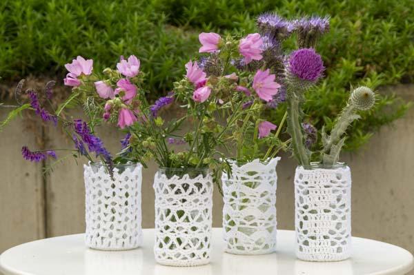 Vier Gläser umhäkelt mit weißem Garn und lila Blüten von Wildblumen